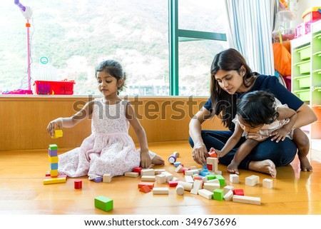 Indian family play toy block together at home - stock photo