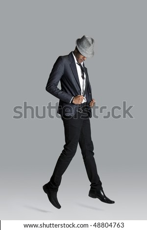 Indian fashion model holds onto his suit jacket as he floats upward - stock photo