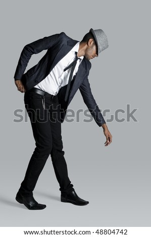 Indian fashion model lets an arm hang as he poses - stock photo