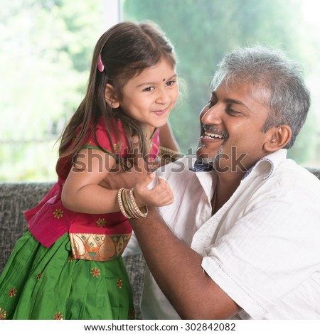 Indian father playing with daughter at home. Asian family indoors living lifestyle. - stock photo