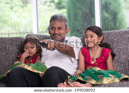 indian father watching tv with his daughter on living room - stock photo