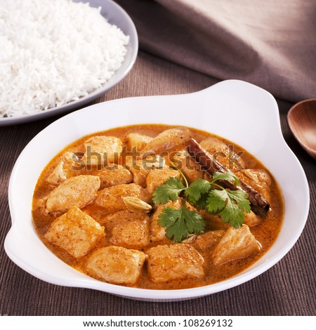 Indian favourite curry, butter chicken, garnished with coriander, cinnamon and cardamom, with basmati rice. - stock photo