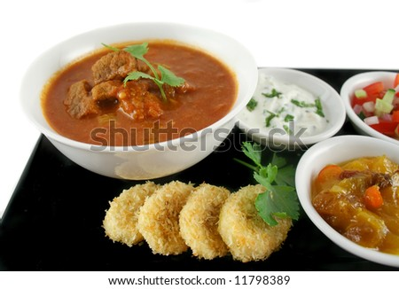 Indian feast of vindaloo curry, mango chutney, banana and coconut, tomato and cucumber. - stock photo