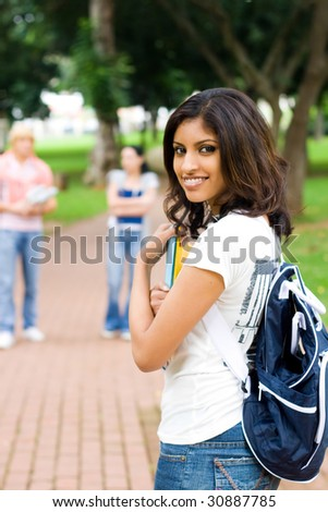 indian female college student in campus, background is her friends - stock photo