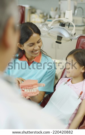 Indian female dental assistant showing model of teeth to young female patient - stock photo