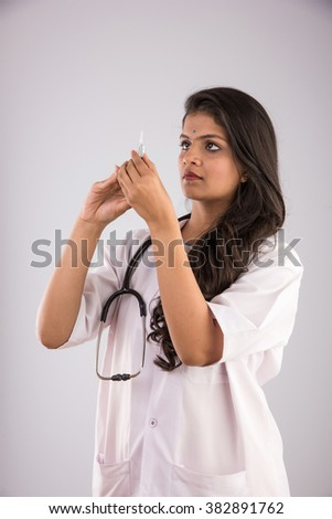 indian Female doctor holding syringe in hand on gray background, asian female doctor with injection