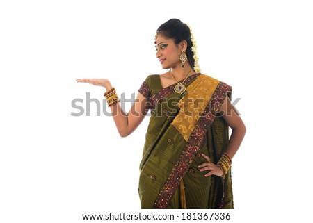 Indian Female wearing sari presenting a product - empty copy space over grey background  - stock photo