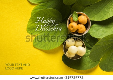 indian festival dussehra, showing golden leaf with traditional indian sweets pedha in silver bowl on yellow background, greeting card - stock photo
