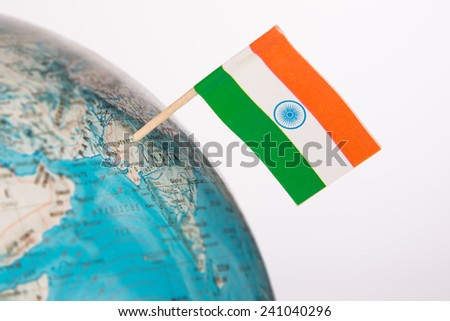 Indian flag pointing on New Delhi in  globe. Shallow depth of field,  - stock photo