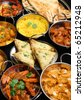 Indian food including curries, rice, samosas and naan bread. - stock photo
