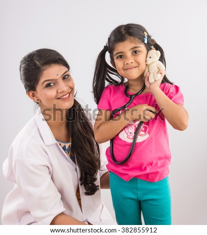 indian girl child with young beautiful female doctor, indian doctor and baby girl, asian doctor with girl, isolated on gray background - stock photo
