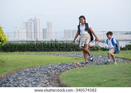 Indian girl holding hand of her cute little brother when they going to school - stock photo