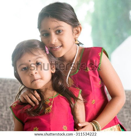 Indian girl hugging her younger sister with love. Asian children at home. Beautiful daughters in traditional India sari. - stock photo