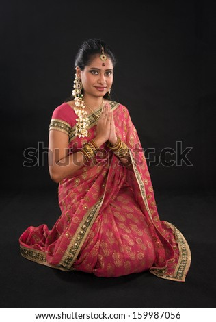 Indian girl in a greeting pose, traditional sari costume, full length kneeling on floor isolated on black background - stock photo