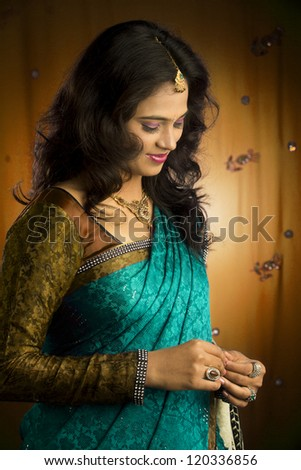 Indian girl in traditional Indian sari posing to the camera. - stock photo
