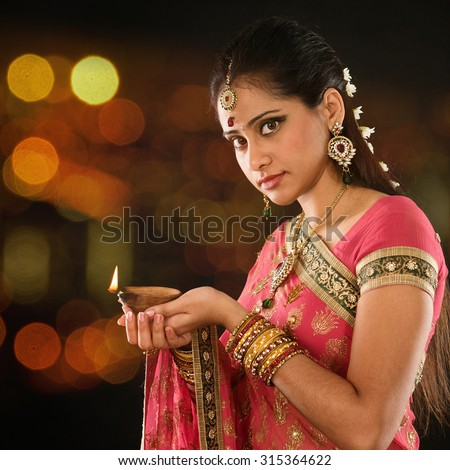 Indian girl in traditional sari lighting oil lamp and celebrating Diwali or deepavali, fesitval of lights at temple. Female hands holding oil lamp, beautiful lights bokeh background. - stock photo