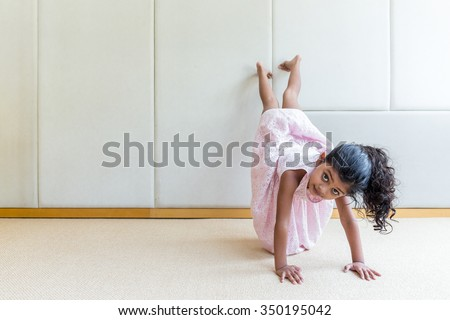 Indian girl playing handstand at home - stock photo