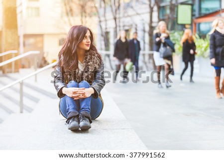 Indian girl portrait in London. She is sitting on a concrete bench with knees pulled up and looking away from camera. On background there are some persons walking on the footpath. - stock photo