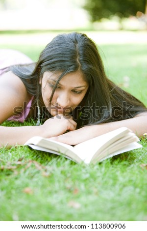 Indian girl reading a book while laying down on green grass in the park. - stock photo
