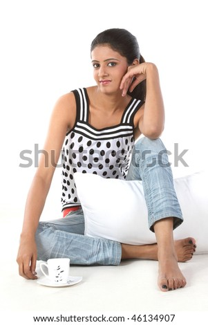 Indian girl sitting with pillow and cup of coffee