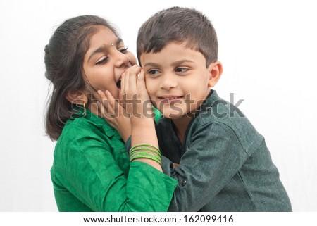 Indian girl whispers boy in the ear secret children gossip - stock photo