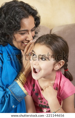 Indian grandmother telling granddaughter a secret
