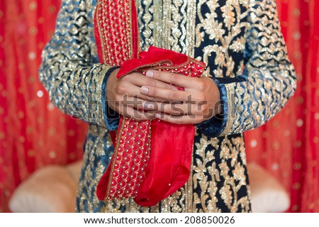 Indian groom holding a scarf in his hands. - stock photo