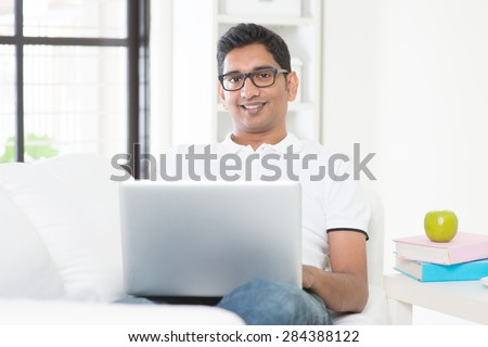 Indian guy with laptop computer working from home. Asian man using internet indoor, relaxed and sitting on sofa. Handsome male model. - stock photo