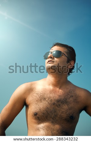 Indian happy young man getting out of the water with sunglasses under blue sky. - stock photo