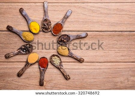 indian herbs on the wood spoon on the wooden table - stock photo