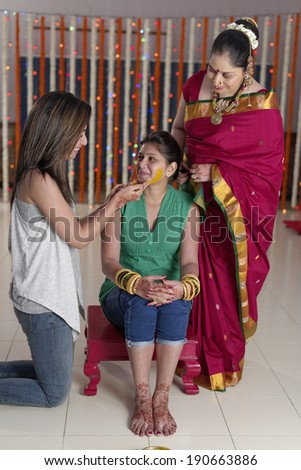 Indian Hindu bride with turmeric paste on her face with mother & sister. - stock photo