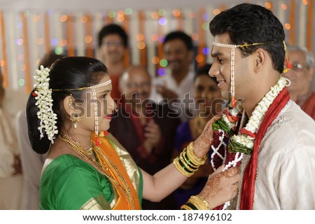 Indian Hindu ritual of exchanging garlands by bride and groom in wedding in Maharashtra. - stock photo