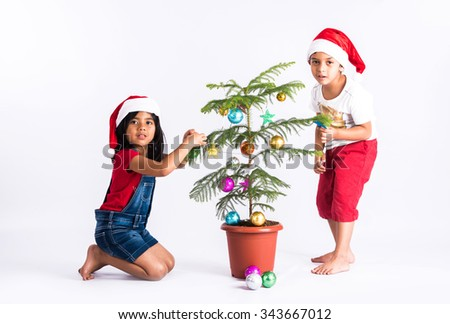 indian little boy and indian little girl standing near decorated christmas tree showing happiness on their face, asian kids and christmas tree, isolated on white background - stock photo