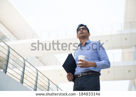 indian male business man holding a coffe with office background - stock photo