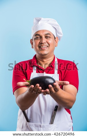 indian male chef cook holding green spinach leaves and egg plant in hand, asian male chef holding fresh vegetables - stock photo