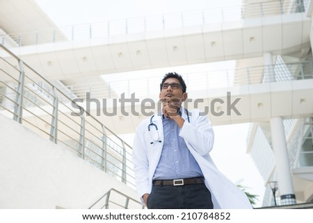 indian male doctor thinking on hospital background  - stock photo