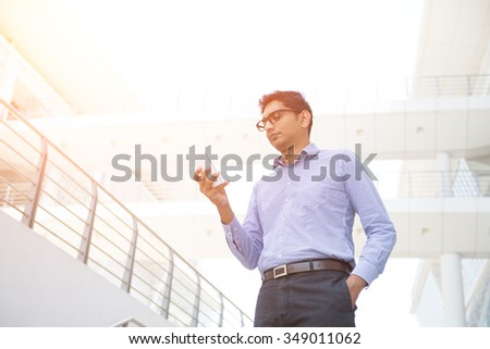 indian male holding a smartphone - stock photo
