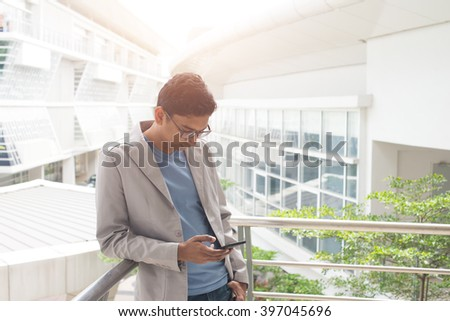 indian male using phone outdoor - stock photo