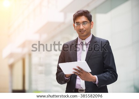 indian male using tablet outdoor - stock photo