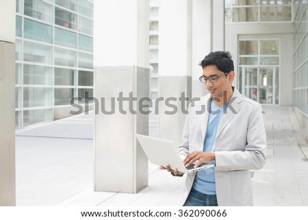 indian male with laptop at outdoor office