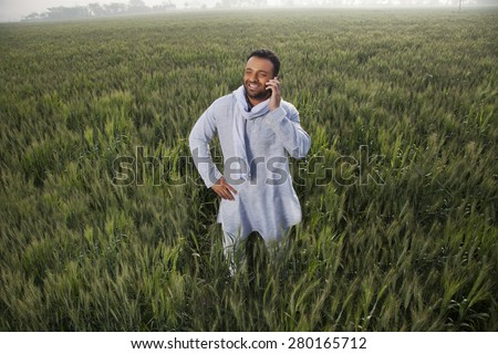 Indian man in a field talking on phone with hand on hip - stock photo