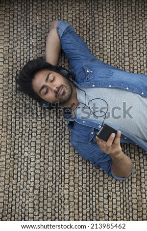 Indian man lying on the floor at home reading his tablet PC. Above view. - stock photo