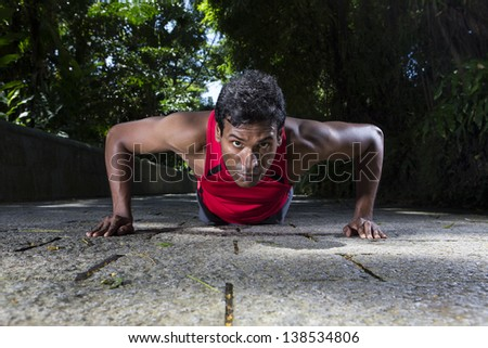 Indian man performing push up in the city park. Male fitness concept. - stock photo