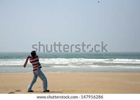 Indian man playing cricket in beach
