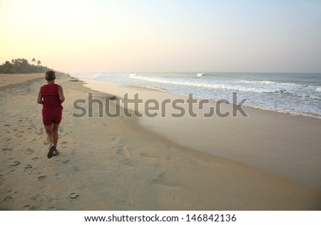 Indian man running along a beach, India