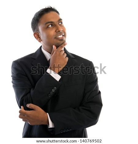 Indian man thinking. Confident young Indian businessman thinking, looking up and standing isolated on white background. - stock photo