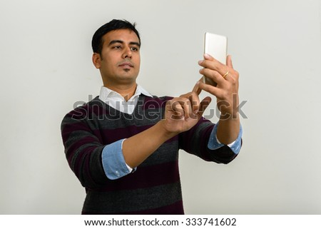 Indian man using mobile phone - stock photo