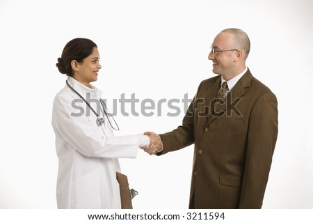 Indian mid adult woman doctor shaking hands with man in business suit. - stock photo