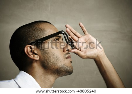 Indian model holds onto his spectacles in studio - stock photo