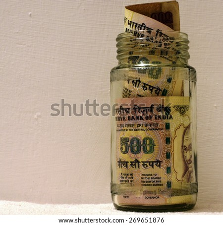 Indian money in glass jar with lot of space for text - stock photo